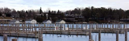 Panoramic photo of a lake town during winter. Lake house new buildings, with view of the marina and cold frozen lake Stock Photos