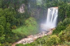 Panoramic photo landscape / Waterfall hidden in the tropical jungle surrounded by a natural swimming pool with clear fresh water. royalty free stock photography