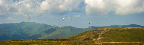 Panoramic photo of a large group of paragliders in the sky above the mountains. Competitions of paragliders on the ridge of Borzhava in the Carpathians in Royalty Free Stock Photography