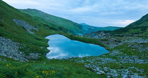 Panoramic photo of a mountain lake in a mountainous rocky valley. Royalty Free Stock Photos