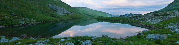 Panoramic photo of a mountain lake in a mountainous rocky valley. Royalty Free Stock Images