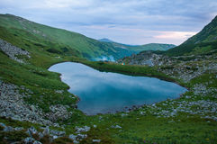 Panoramic photo of a mountain lake in a mountainous rocky valley. Stock Photos