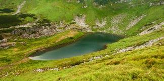 Panoramic photo of a mountain lake in a mountainous rocky valley. Stock Photo