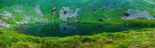 Panoramic photo of a mountain lake in a mountainous rocky valley. Royalty Free Stock Image