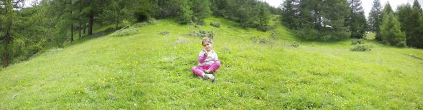 Panoramic photo of mountain landscape in Valtellina, little girl. In the meadow, mountains in spring, path, Bormio, Lombardy, Italy Stock Images