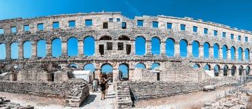 Panoramic photo of Pula Arena, Istria, Croatia. PULA, CROATIA – AUGUST 10, 2018: Tourists admire Pula Arena - ancient amphitheater located in Pula, Istria stock images