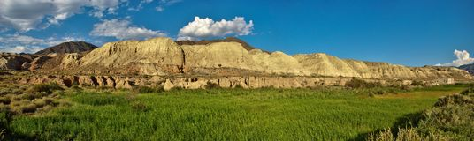 Panoramic photo of the ridge of the canyons yellow, summer green field and blue sky morning stock image