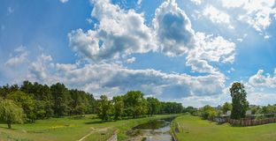 Panoramic photo of the river near the forest under the blue cloudy sky. Panoramic photo of river near the forest under the blue cloudy sky in Ukraine Royalty Free Stock Photos