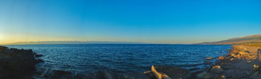 Panoramic photo of the rocky shore of the lake in the early morning, with waves, mountains and clouds on the horizon. stock image