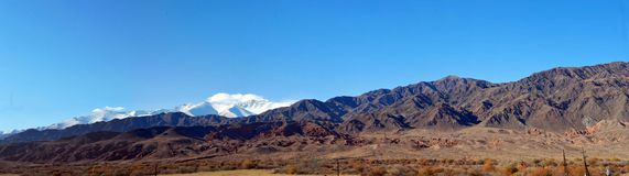 Panoramic photo of a snowy mountain range in the early morning. stock photo