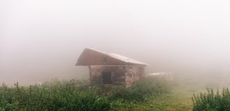 Panoramic photo of wooden house in forest in thick fog, mysterious atmosphere royalty free stock photography