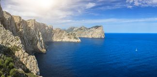 A panorama of the cliffs on the coastline of Pollença, Mallorca and a single white sailboat on the beautiful blue waters. A panoramic picture of the Royalty Free Stock Photos