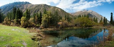 Panoramic picture, a Pond with a small wooden bridge among the trees in the mountains. royalty free stock photos