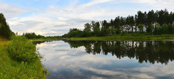 A panoramic picture. Summer landscape. Evening on the river. Reflection of clouds and sky in the water. Royalty Free Stock Images