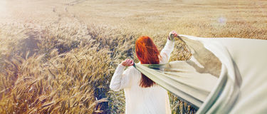 Panoramic picture of walking red hair woman by the plain field Royalty Free Stock Images