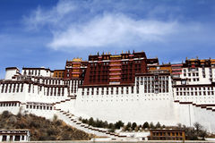 The panoramic of the Potala Palace, with the people republic of China flag inside as well as Potala Palace square, trees and meado Royalty Free Stock Image