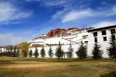 The panoramic of the Potala Palace, with the people republic of China flag inside as well as Potala Palace square, trees and meado Stock Image