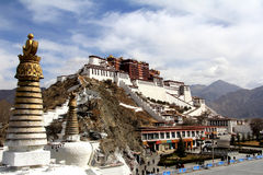 The panoramic of the Potala Palace, with the people republic of China flag inside as well as Potala Palace square, trees and meado Stock Photo