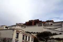 The panoramic of the Potala Palace, with the people republic of China flag inside as well as Potala Palace square, trees and meado Stock Photography
