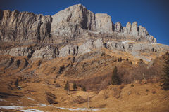 Panoramic rocky landscape of Alps with snow and trees and blue s Royalty Free Stock Photo