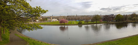 Panoramic romantic view of Inverleith Park, Edinburgh, Scotland. Panoramic romantic view of pond, trees and walkway at Inverleith Park in Edinburgh, Scotland, on royalty free stock images