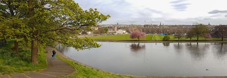 Panoramic romantic view, walking couple at Inverleith Park, Edin. Panoramic romantic view of couple walking along pond at Inverleith Park in Edinburgh, Scotland royalty free stock images