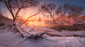 Panoramic russian winter landscape with forest, beautiful frozen river at sunset. Scenery with winter trees, water and blue sky