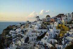 Panoramic scene in evening light of Oia windmill and white building townscape along island mountain facing vast ocean royalty free stock image
