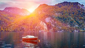 Panoramic scenic sunset over calm and peaceful Austrian alps lake. Red lonely boat or yacht in the evening sunlight with clouds royalty free stock photography