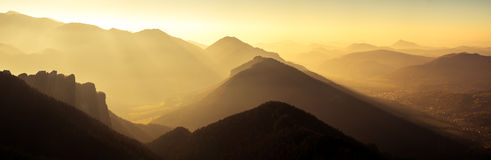 Panoramic scenic view of mountains and hills silhouette at sunse Stock Image