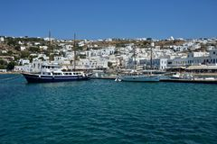 Panoramic seaside view of Mykonos with white buildings and harbor with sailing ship royalty free stock photo
