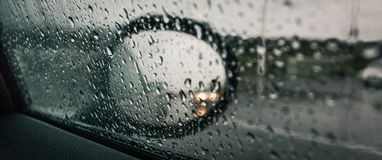 Panoramic shot of a car`s side-view mirror with the window covered in raindrops stock images