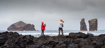 Panoramic shot from a Couple of tourists, photographing the Mosteiros Volcanic Beach. In Sao Miguel, Azores, Portugal Stock Image