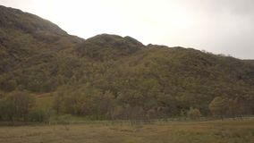 Panoramic shot of a dramatic view of the Glen Nevis. Starting with a view of the hills and ending with a view of the falling waters. The shot pans at stock video footage