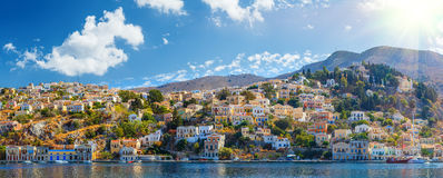 Panoramic shot of the Harbour at Symi Greece with a traditional fishing boat in the foreground.  Europe. Stock Photography