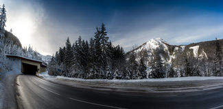Panoramic shot of highway in snowy mountains with long turn Royalty Free Stock Photography