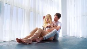 Panoramic shot of lovely couple in pajamas sitting on floor with domestic bunny. Near big curtained window. happy people spending leisure time together with stock video