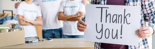 Panoramic shot of man holding card with thank you inscription while standing near volunteers.