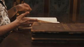 Panoramic shot old woman leaf through book russian cursive text on table. Panoramic shot an old woman leaf through book russian cursive text on table stock footage