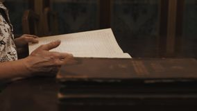 Panoramic shot old woman thumb through book russian cursive text on table stock footage