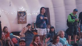 Panoramic shot of people applauds sitting on bean bags inside of a tent. During festival event. Changing colorful lights stock footage