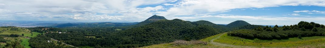 Panoramic shot of puy de dome. Panoramic view of the puy de dome with clouds and walkers Royalty Free Stock Photos