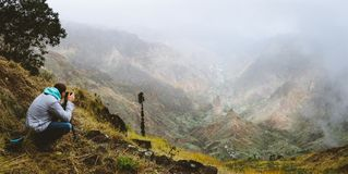 Panoramic shot of traveler making photo of amazing steep mountainous terrain with lush canyon valley on the path from Xo. Xo Valley. Cloudy sky. Santo Antao Stock Photo
