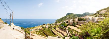 Landscape and historic village against blue sea and sky on Mallorca. Panoramic shot of typical village and landscape against blue sea and sky on island of Stock Photo