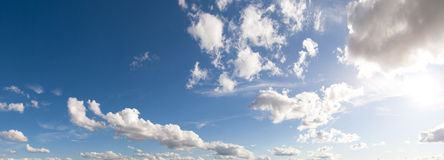 Panoramic sky. A panoramic background of blue skies with some clouds and bright sun Stock Photography