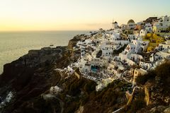 Panoramic skyline scene in sunset light of Oia village and white building townscape along island natural mountain facing ocean royalty free stock photo
