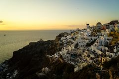 Panoramic skyline scene in sunset light of Oia windmill and white building townscape along island natural mountain facing ocean royalty free stock photography