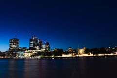 Panoramic skyline view of Bank and Canary Wharf, central London`s leading financial districts with famous skyscrapers at golden h. London, England - Panoramic royalty free stock photo