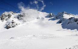 Panoramic snow mountains view. A panoramic view on Alpes massif of snow mountains with cabine cables coming to top. Alpes, Switzerland, Europe Royalty Free Stock Photo