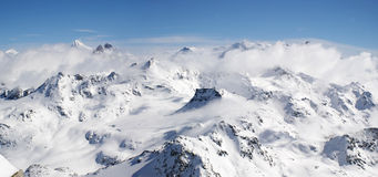 Panoramic snow mountains view. A panoramic view on Alpes massif of snow mountains under slouds. Alpes, Switzerland, Europe Stock Images